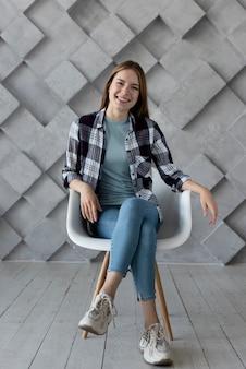 Kobieta pozuje na krześle dla kamery