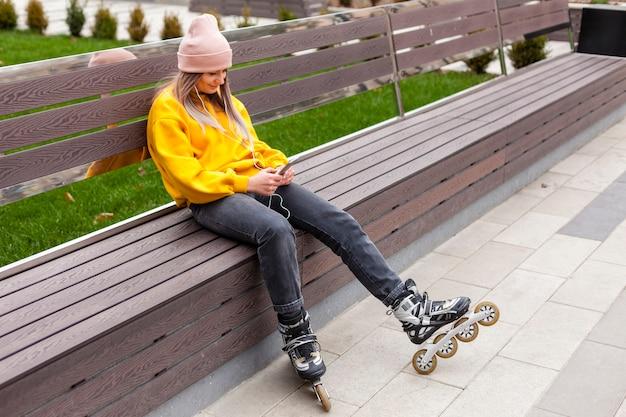 Kobieta pozuje na ławce podczas gdy będący ubranym rolkowych ostrza
