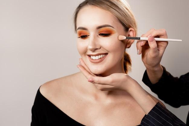Kobieta pozuje na lekkim pracownianym tle. ręce charakteryzatora korygują makijaż specjalnym pędzlem. profesjonalny makijaż