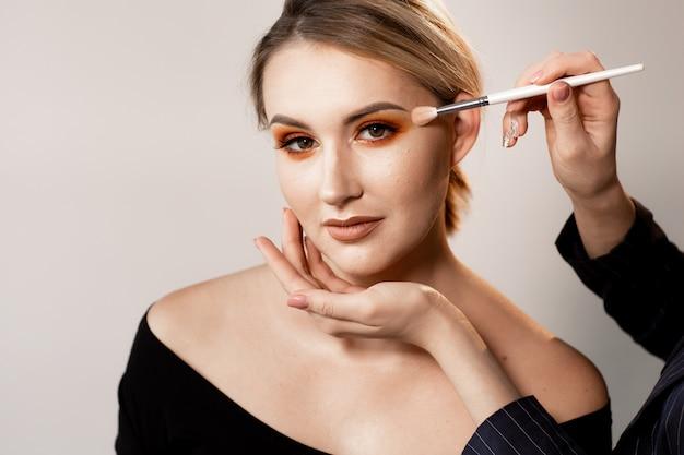 Kobieta pozuje na lekkim studiu. ręce charakteryzatora korygują makijaż specjalnym pędzlem. profesjonalny makijaż