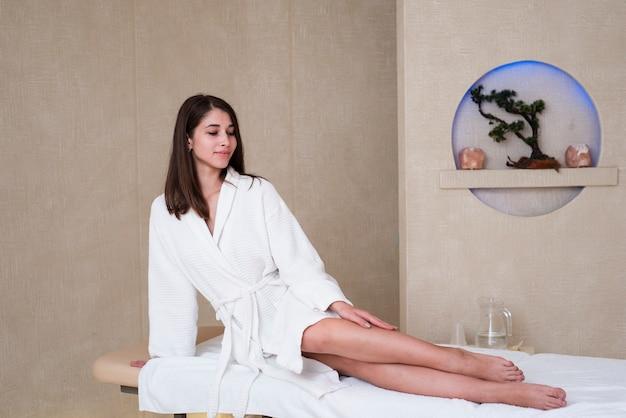 Kobieta pozuje na masażu stole przy zdrojem