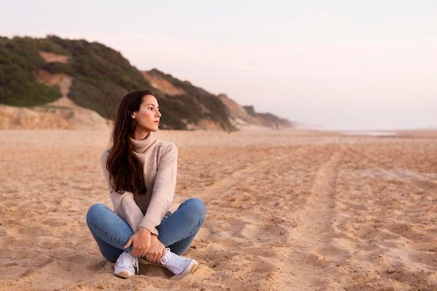 Kobieta pozuje na piasku na plaży z miejsca na kopię