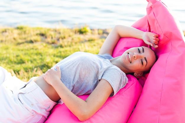 Kobieta pozuje na różowym beanbag