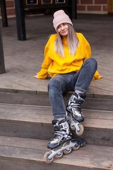 Kobieta pozuje na schodkach z rolkowymi ostrzami