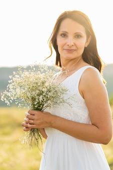 Kobieta pozuje na zewnątrz z kwiatami