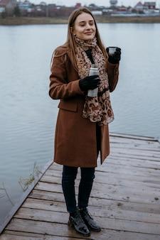 Kobieta pozuje nad jeziorem z gorącym napojem