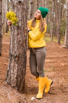 Kobieta pozuje obok drzewa, odwracając wzrok