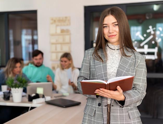 Kobieta pozuje obok swoich współpracowników