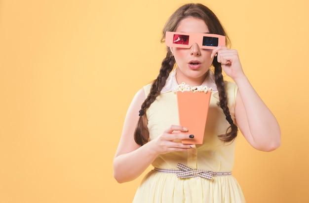 Kobieta pozuje podczas gdy będący ubranym filmów szkła i trzymający popkorn