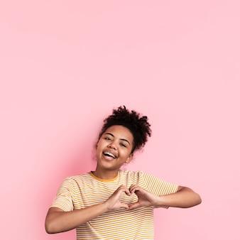 Kobieta pozuje podczas gdy robić w kształcie serca znakowi