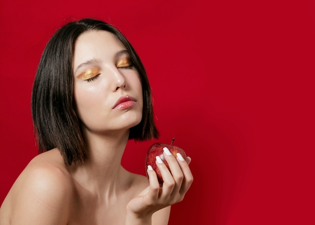 Kobieta pozuje podczas gdy trzymający jabłka