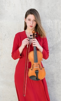 Kobieta pozuje podczas gdy trzymający skrzypce i łęk