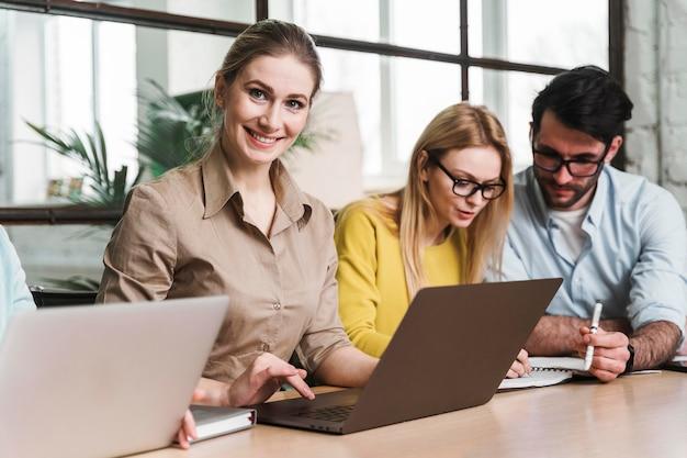 Kobieta pozuje podczas spotkania w pomieszczeniu z laptopem