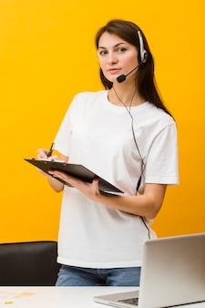 Kobieta pozuje przy biurkiem podczas gdy będący ubranym słuchawki i pisze coś puszku