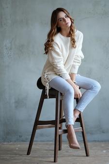 Kobieta pozuje siedzieć na krześle