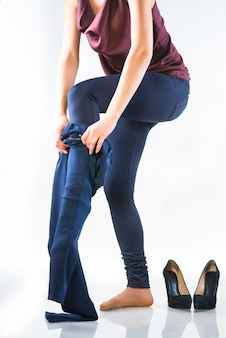 Kobieta Pozuje Stojąc Boso I Trzymając Legginsy W Dłoniach. Pełnometrażowe Zdjęcie Na Białym Tle Premium Zdjęcia