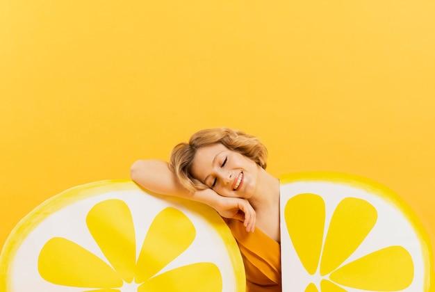 Kobieta pozuje szczęśliwie z cytryną pokrajać dekoracje