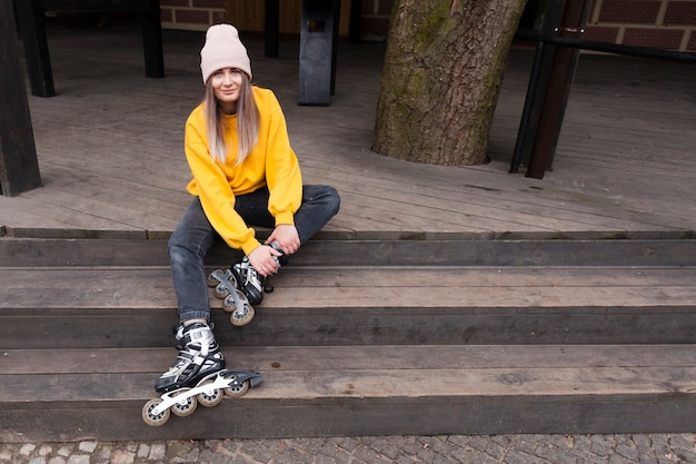Kobieta pozuje szczęśliwie z rolkowymi ostrzami na schodkach