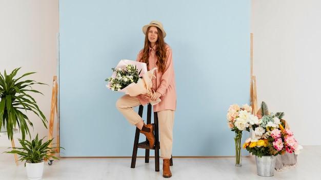 Kobieta pozuje trzymając bukiet wiosennych kwiatów