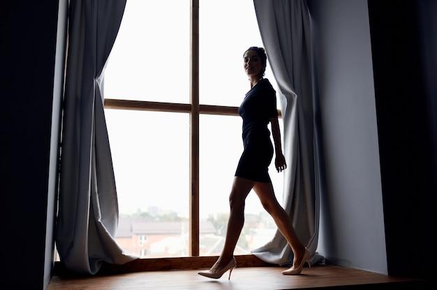 Kobieta pozuje w pobliżu eleganckiego uroku okna
