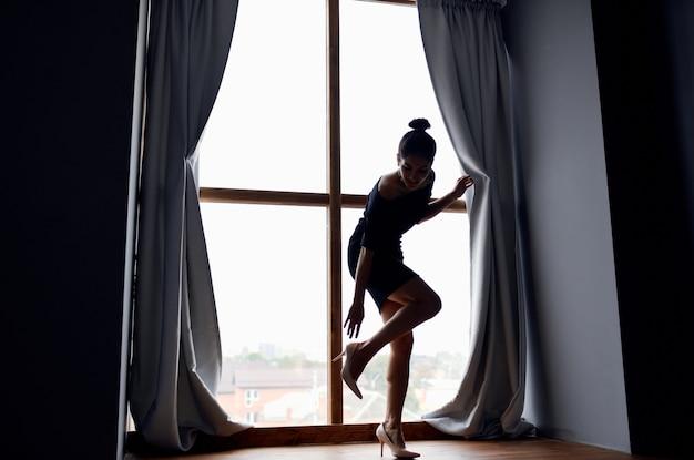 Kobieta pozuje w pobliżu modelu wnętrza domu w oknie