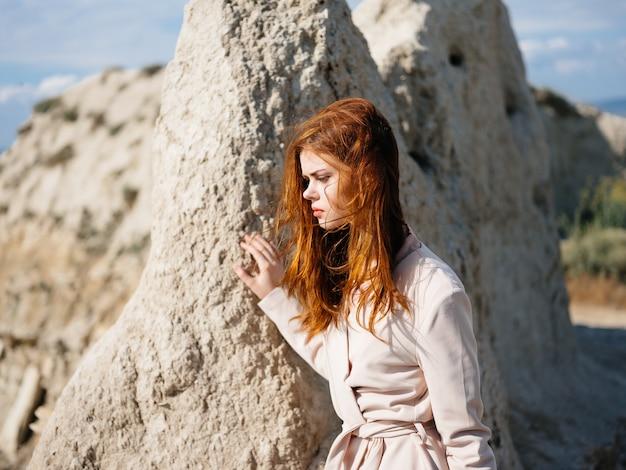 Kobieta pozuje w pobliżu skał na piasku atrakcyjny wygląd