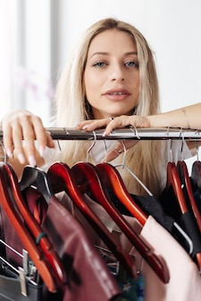 Kobieta pozuje w pobliżu wieszak na ubrania z wieszakami i modne ubrania na białym pokoju