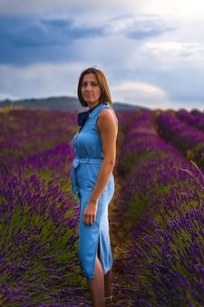 Kobieta pozuje w polach kwiatów lawendy