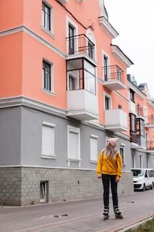 Kobieta pozuje w rolkowych ostrzach obok budynków