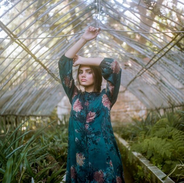 Kobieta pozuje w zielonym domu