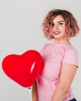 Kobieta pozuje z balonem dla walentynka dnia