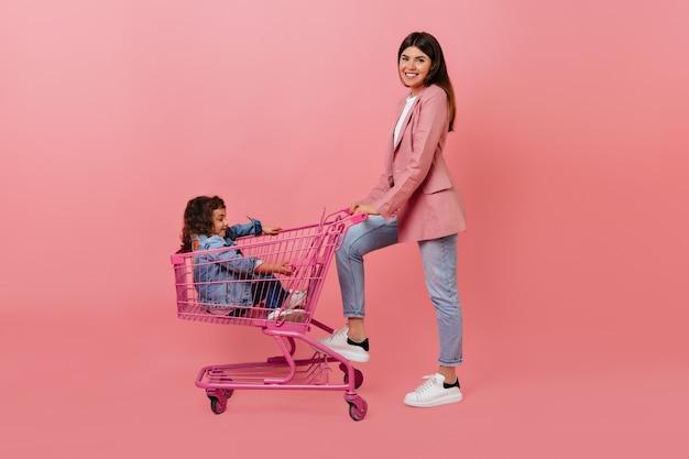 Kobieta pozuje z córką po zakupach. beztroska preteen dziewczyna siedzi w koszyku.