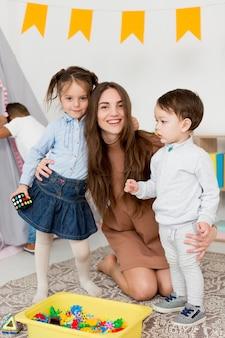 Kobieta pozuje z dziećmi i zabawkami