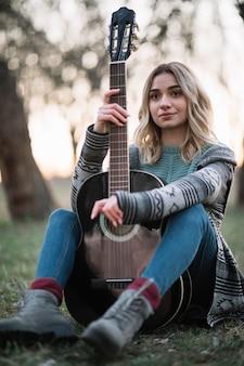 Kobieta pozuje z gitarą