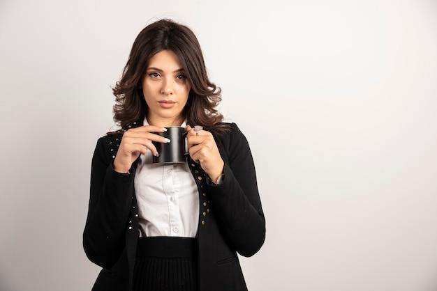 Kobieta pozuje z herbatą na białym