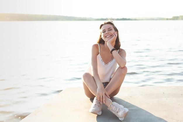 Kobieta pozuje z jej oczami zamykającymi obok jeziora