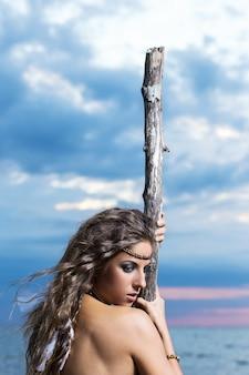 Kobieta pozuje z kijem