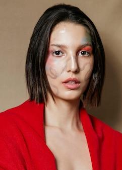 Kobieta pozuje z malującą twarzą i oko cieniem