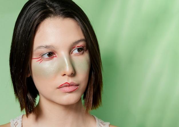 Kobieta pozuje z malującą twarzą