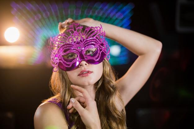 Kobieta pozuje z maskaradą w barze