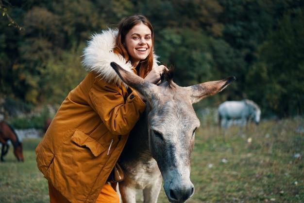 Kobieta pozuje z osłem na naturze w górach