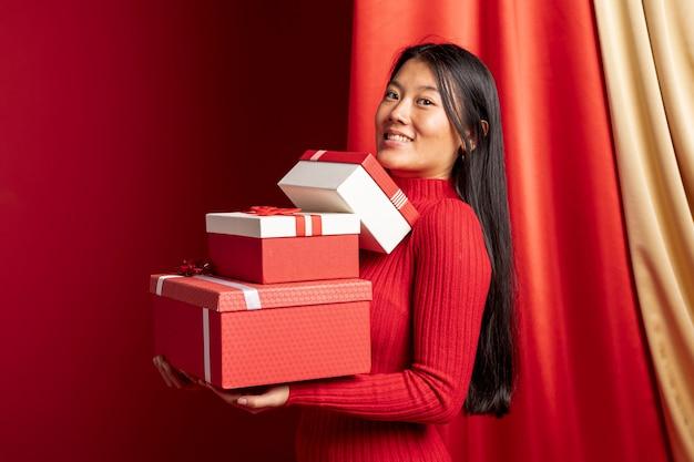 Kobieta pozuje z pudełkami dla chińskiego nowego roku