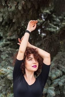 Kobieta pozuje z rękami w górę