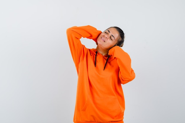 Kobieta pozuje z rękami za głową w pomarańczowej bluzie z kapturem i wygląda spokojnie