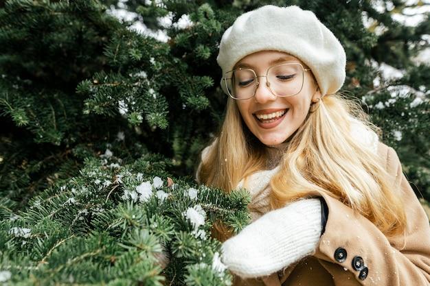 Kobieta pozuje z roślinnością w parku zimą