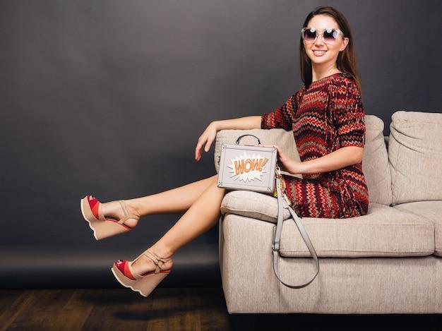 Kobieta pozuje z stylowe obuwie letnie mody i torby