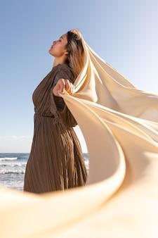 Kobieta pozuje z tkaniny średnim strzałem