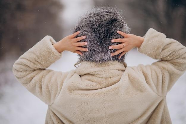 Kobieta pozuje z tyłu i spaceruje w parku zimowym