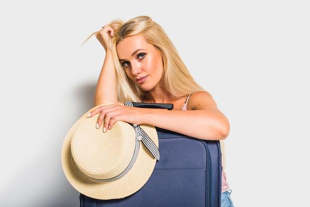 Kobieta pozuje z walizką