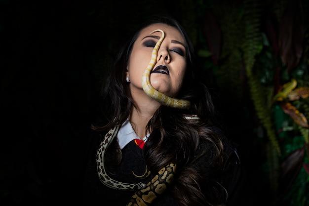 Kobieta pozuje z wężem na zmrok ścianie